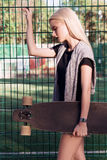 Beautiful sport girl with a longboard. A young girl walks and rides a longboard Stock Photography