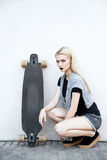 Beautiful sport girl with a longboard. A young girl walks and rides a longboard Royalty Free Stock Photography