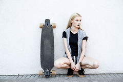 Beautiful sport girl with a longboard. A young girl walks and rides a longboard Stock Photo