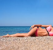 Beautiful sport woman sunbathing on the beach. Beautiful sport slim woman near the sea,  posing Royalty Free Stock Photo
