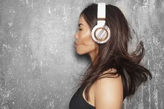 Beautiful sport woman with big white headphones. Model listening the music. Fitness portrait, perfect body shapes Stock Photos
