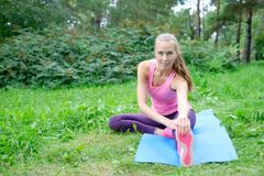 Beautiful sport woman doing stretching fitness exercise in city park at green grass. Yoga postures. Beautiful sport woman doing stretching fitness exercise in Royalty Free Stock Image