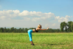 Beautiful sport woman doing stretching fitness exercise in city park at green grass. Royalty Free Stock Photos