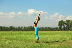 Beautiful sport woman doing stretching fitness exercise in city park at green grass. Stock Photography