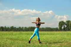 Beautiful sport woman doing stretching fitness exercise in city park at green grass. Yoga postures Royalty Free Stock Photography