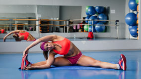 Beautiful sport woman doing stretching fitness exercise at sport gym. Yoga Stock Images