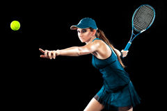 Beautiful sport woman tennis player with racket in blue costume. Beautiful girl tennis player with a racket on dark background wiht lights Stock Image