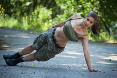 Beautiful sport woman training one arm pushup in p Royalty Free Stock Image