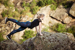 Beautiful sportive blonde girl stretching on rock in canyon. Beautiful sportive blonde girl training on rock in canyon. Copy space Stock Image