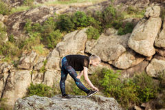 Beautiful sportive blonde girl training, stretching on rock in canyon. Royalty Free Stock Image