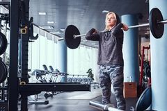 Beautiful sportive girl wearing hoodie doing squats with barbell in the modern gym royalty free stock photos
