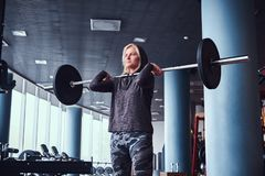 Beautiful sportive girl wearing hoodie doing squats with barbell in the modern gym stock images