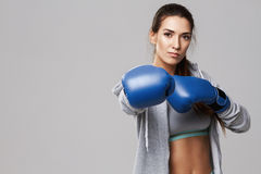 Beautiful sportive girl looking at camera wearing blue box gloves training over white background. Copy space Royalty Free Stock Image