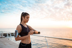 Beautiful sportive girl looking at watch during sunrise over seaside. Royalty Free Stock Images