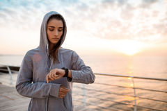 Beautiful sportive girl looking at watch during sunrise over seaside. Royalty Free Stock Photography