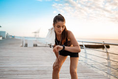 Beautiful sportive girl looking at watch during sunrise over seaside. Stock Image