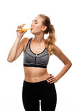 Beautiful sportive girl posing, drinking juice over white background. Stock Photos