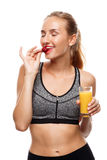 Beautiful sportive girl posing, holding glass of juice and eating strawberry over white background. Stock Photography