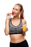 Beautiful sportive girl posing, holding glass of juice and eating strawberry over white background. Royalty Free Stock Image