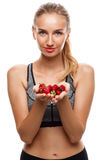 Beautiful sportive girl posing, holding strawberry over white background. Royalty Free Stock Images