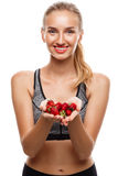 Beautiful sportive girl posing, holding strawberry over white background. Stock Photos