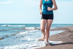 Beautiful sportive girl running along beautiful sandy beach, hea. Lthy lifestyle Stock Image