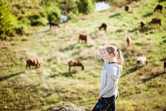 Beautiful sportive girl standing on rock. Field with cows background. Stock Images