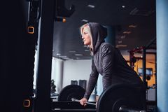Beautiful sportive girl wearing hoodie leaning on a barbell next to a stand and looking sideways royalty free stock photo