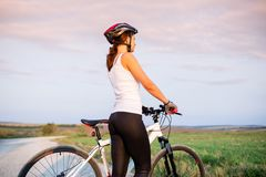 A sports girl with a bike looking at the horizon. A beautiful sports girl with a bike looking at the horizon Royalty Free Stock Images