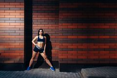 Beautiful sports girl posing against a brick wall background. stock image