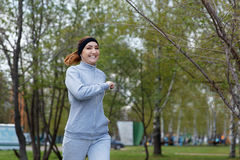 Beautiful sports girl runs in park and listening to music Royalty Free Stock Photography