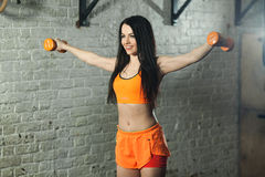 Beautiful sports girl. Beautiful young girl in bright sports clothes with dumbbells in hands in a sports hall Stock Photography