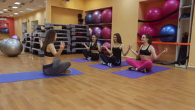 Beautiful sports people are sitting in lotus position and smiling. stock video