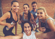 Beautiful sports team. Are holding sports equipment, looking at camera and smiling while doing selfie in fitness hall Royalty Free Stock Image