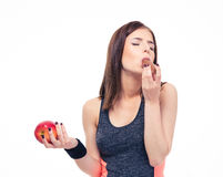 Beautiful sports woman holding apple and eating chocolate Stock Images