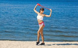 A beautiful sports woman holds a red rope in his hands is engaged in gymnastics. Against the background of the sea coast Royalty Free Stock Image