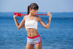 A beautiful sports woman holds a red rope in his hands is engaged in gymnastics. Against the background of the sea coast Stock Photo