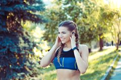 Beautiful sportswoman with headphones in park stock images