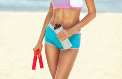 A beautiful sportswoman holds a bottle of water and a red skipping rope in her hands, on her shoulder lies a white towel Royalty Free Stock Images