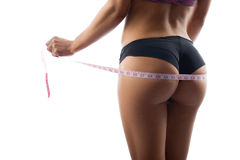 Beautiful sportswoman measuring her hips royalty free stock photography