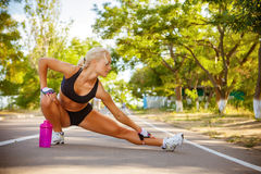 Beautiful sportswoman outdoor doing exercises Stock Photography