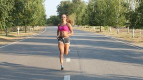Beautiful sportswoman running on a country road. Training outdoors. Beautiful sportswoman running on a country road, training outdoors, athletic body, trees on stock video