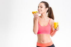 Beautiful sportswoman smelling orange and holding glass of juice Stock Photo