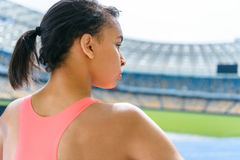 Beautiful sportswoman standing on running track stadium and looking away. Young beautiful sportswoman standing on running track stadium and looking away Royalty Free Stock Images