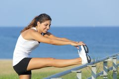 Beautiful sportswoman stretching with the sea in the background Stock Photo
