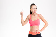 Beautiful sportswoman in tracksuit pointing up and having an idea Royalty Free Stock Photo