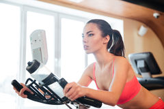 Beautiful sportswoman training on bicycle in gym Stock Photos
