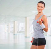 Beautiful sportswoman wearing sports clothes holding weights Stock Photo