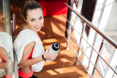 Beautiful sportswoman with white towel drinking water in gym Royalty Free Stock Images