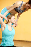 Beautiful sportswomen doing stretching exercises. In gym Royalty Free Stock Photos